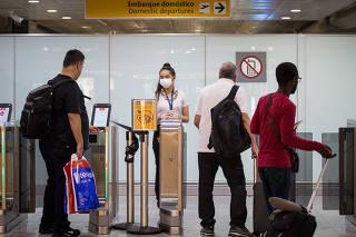 Pessoas usam máscaras no aeroporto de Guarulhos
