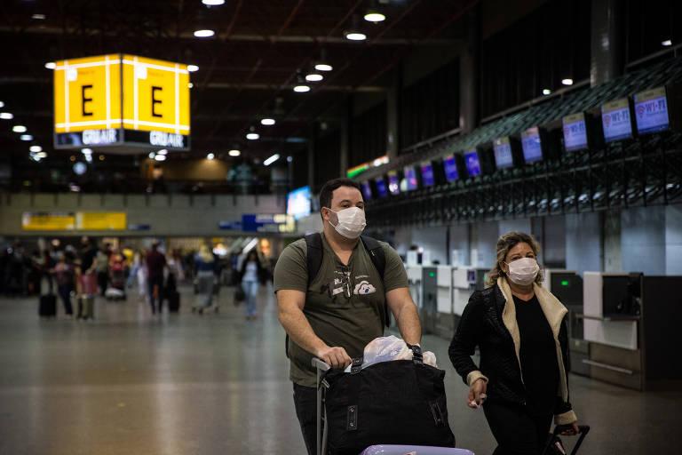 Casal com máscara cirúrgica empurra malas em saguão de aeroporto