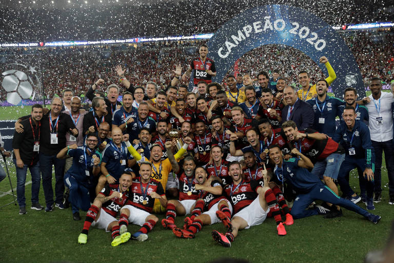 Equipe do Flamengo posa para foto em gramado em frente a arquibancada