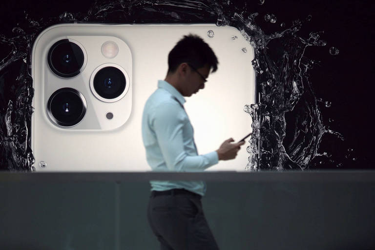 Homem anda em frente a um anúncio do iPhone 11 Pro