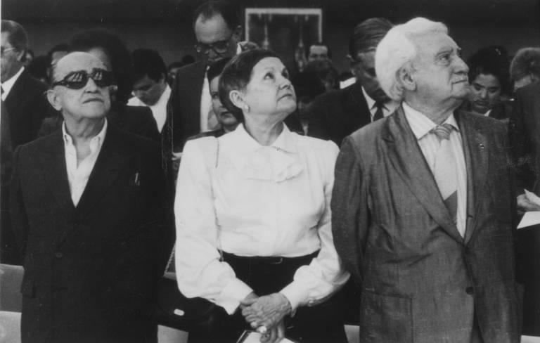 dois homens e uma mulher olham para o lado e vestem  roupas formais
