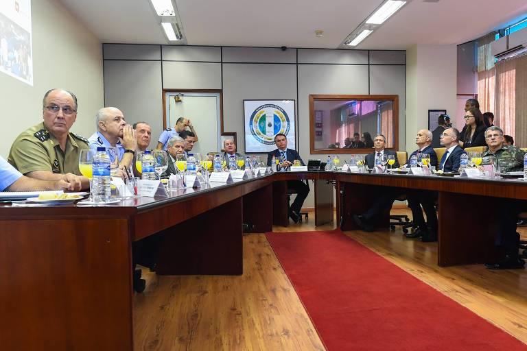 Sentados à mesa, Bolsonaro, no centro da imagem, cercado por ministros militares