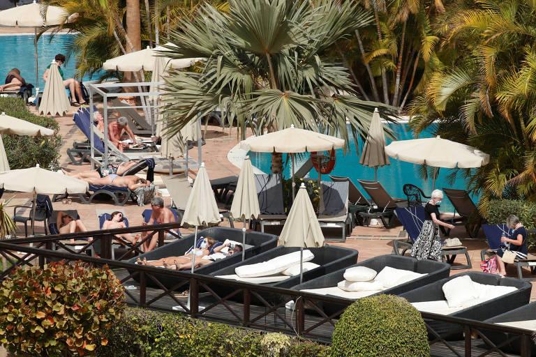 Pessoas deitadas em espreguiçadeiras na piscina de um hotel, algumas sem máscara e outras com