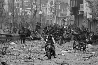 Men ride a motorcycle past security forces patrolling a street in a riot affected area after clashes erupted between people demonstrating for and against a new citizenship law in New Delhi