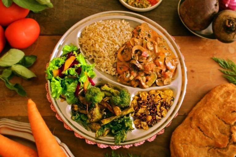 Estrogonofe de cogumelos, servido às quintas-feiras; acompanha arroz integral, pakora (legumes empanados), granola salgada, salada e pavê de paçoca de sobremesa.