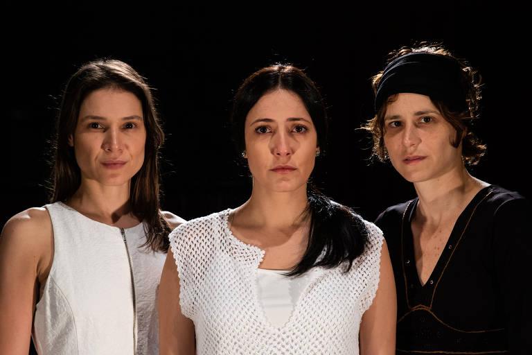 três mulheres sérias em fundo preto