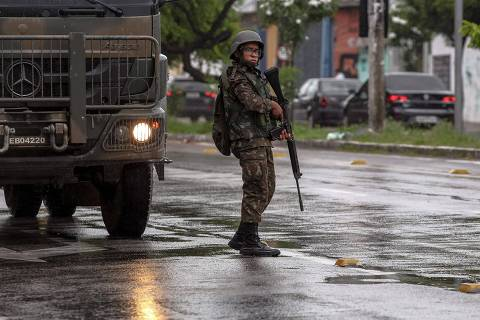 A Brazilian Armed Forces soldier stands guard next to a military truck in the streets of Fortaleza, Ceara state, Brazil, on February 22, 2020. - 51 homicides were registered in 48 hours in the northeastern state of Ceara since the military police there is on strike in demand of better salaries, informed the regional Security Secretariat Friday. (Photo by JARBAS DE OLIVEIRA / AFP)