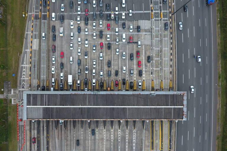 Foto aérea mostra fileiras de carros em pedágio em rodovia