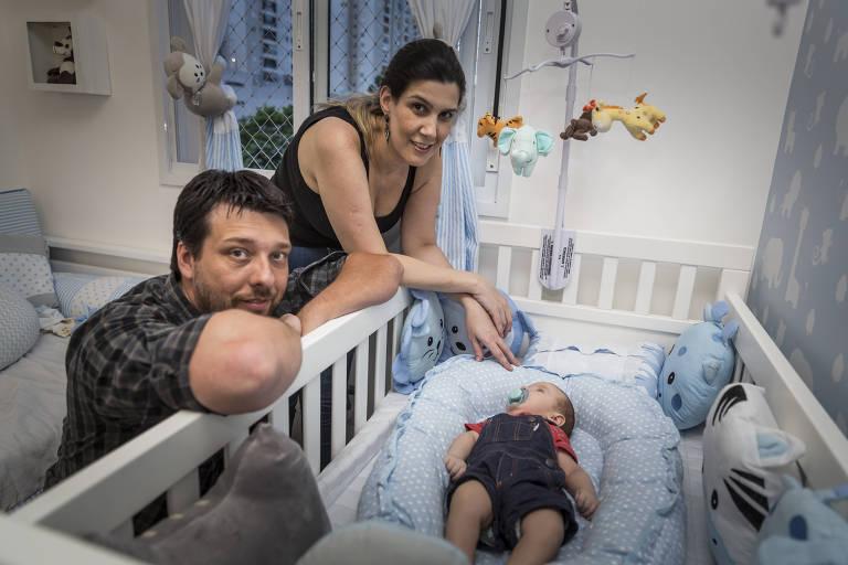 O casal Betania Mazzini e Andre Santana observa João no berço