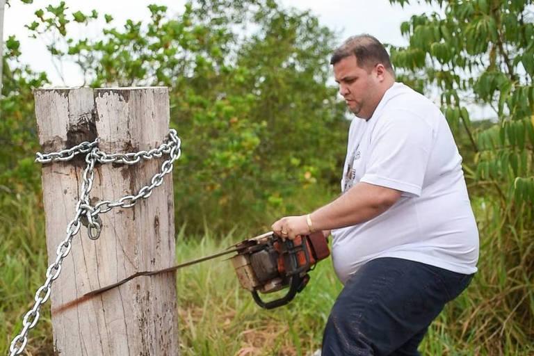 O deputado estadual Jeferson Alves (PTB-RR) serra o tronco e corta a corrente que bloqueava o acesso à BR-174