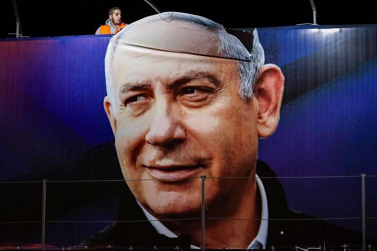 Funcionário ajeita outdoor em Jerusalém do premiê Binyamin Netanyahu