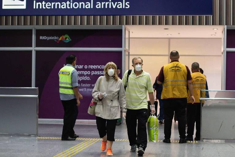 Passageiros usando mascaras desembarcam no sábado (29), vindos de Roma, Itália, país que vivencia surto do novo coronavírus