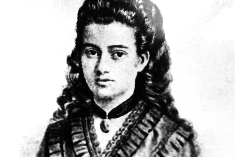 Retrato antigo, em preto e branco, de uma jovem de cabelos escuros, cacheados e longos. Ela usa uma gargantilha no pescoço e um vestido com laço no decote.