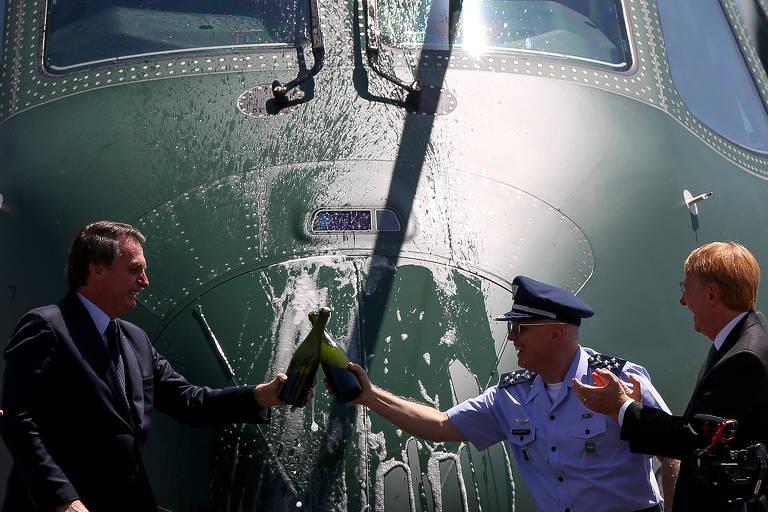 O presidente Bolsonaro e Antônio Bermudez, da FAB, observados por Jackson Schneider, da Embraer, estouram champanhe para batizar o avião KC-390