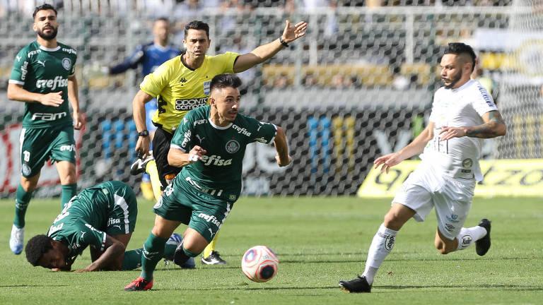 O atacante Willian, do Palmeiras, carrega a bola sob a marcação do lateral santista Pará, em jogo pelo Campeonato Paulista