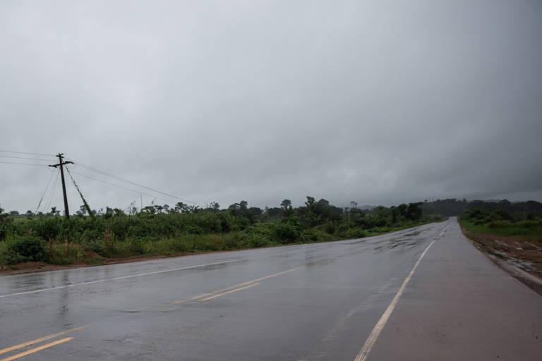 Pista de rodovia de mão dupla, com uma faixa, molhada de chuva, com nuvens carregadas no céu