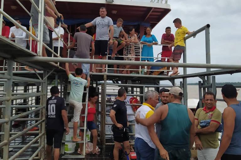 Cerca de 30 pessoas, quase todos homens, parados em um barco
