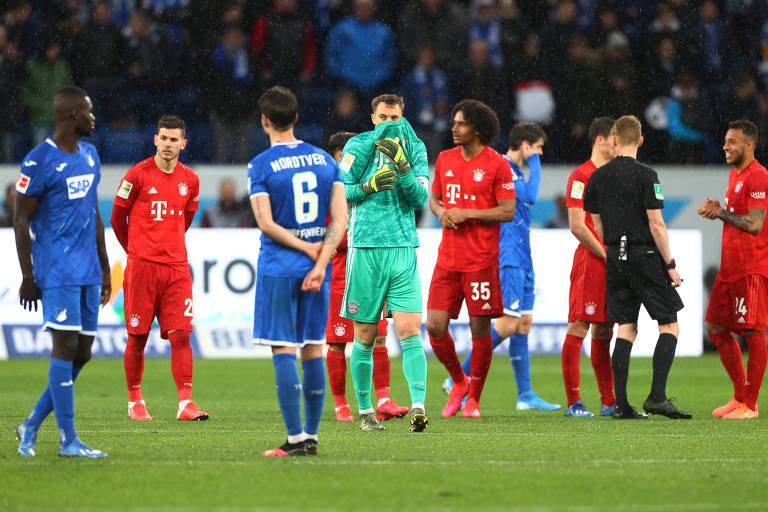 Jogadores do Bayern de Munique e do Hoffenheim cruzam os braços e conversam durante paralisação de jogo pelo Campeonato Alemão após protestos de torcedores bávaros contra o dono do Hoffenheim