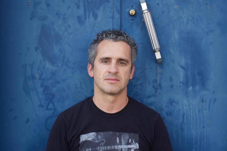 homem de camiseta preta em frente a parede azul