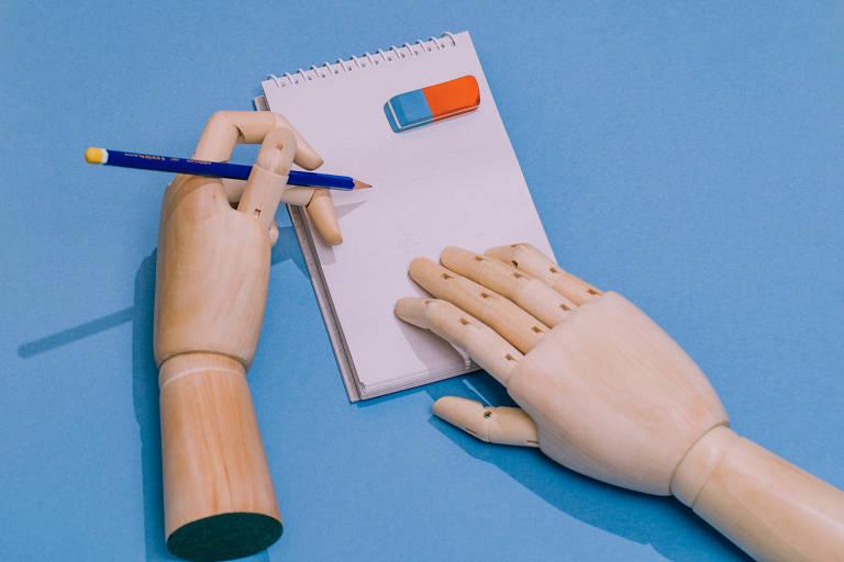 Mãos de madeira estão disposta em uma mesa. Uma delas segura um lápis enquanto a outra está apoiada em um caderno