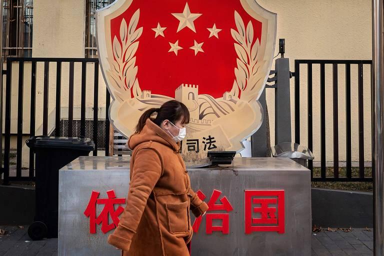 Mulher anda em rua de Pequim usando máscara na China