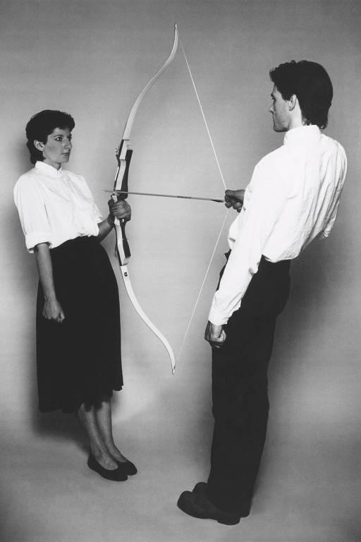 Homem segura arco e flecha apontado para mulher