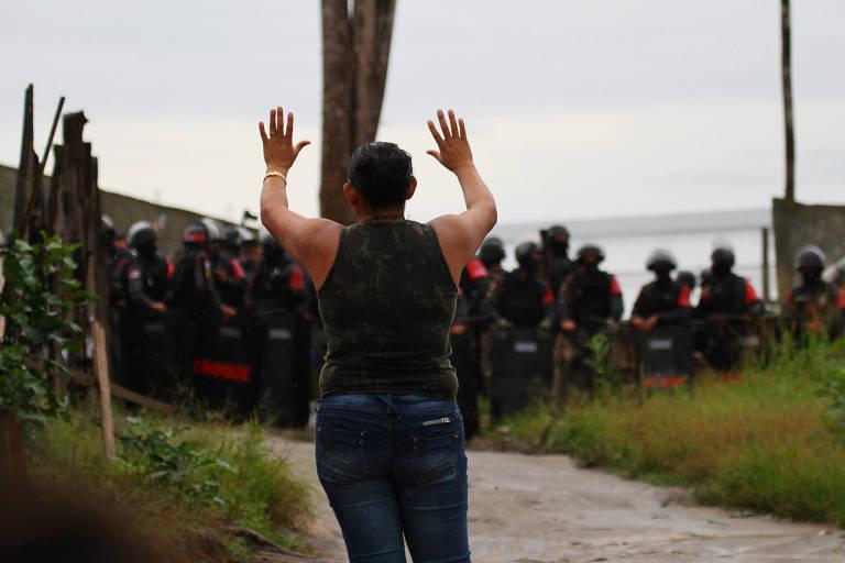Moradora faz oração durante negociação para a entrada de policiais para reintegração de posse da invasão Monte Horebe, em Manaus