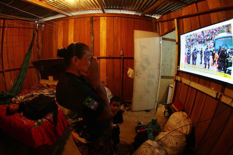 A moradora Leuda Mota, 49, assiste na televisão reportagens sobre a reintegração de posse da invasão