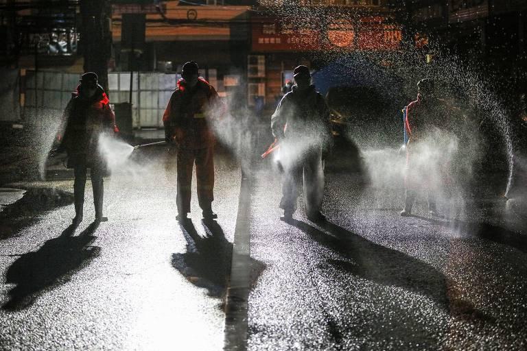 Trabalhadores desinfetam uma rua na cidade de Xiaogan, província de Hubei, na China