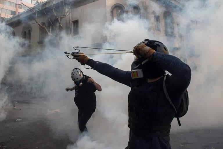 Manifestante lança pedra contra polícia em protesto em Santiago