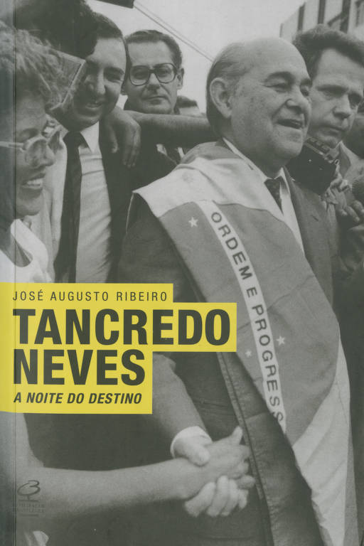Tancredo Neves está com a bandeira do Brasil estendida nos ombros e aperta as mãos de pessoas
