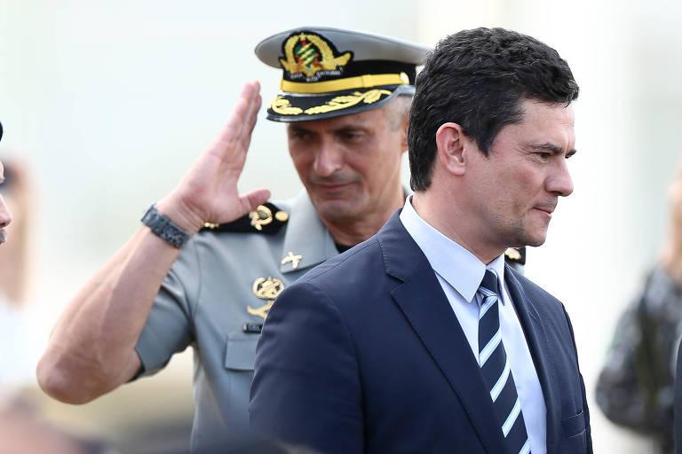 Aginaldo aparece fardado, ao fundo, prestando continência; Moro está à frente, de perfil, trajando terno e gravata
