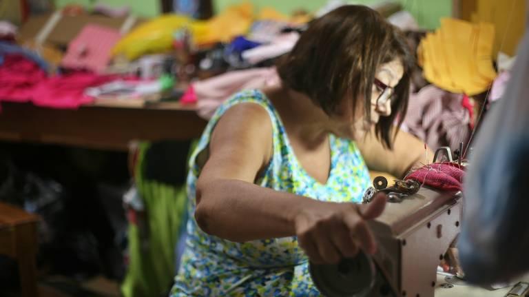 Costureira entre peças de tecido e uma máquina de costura