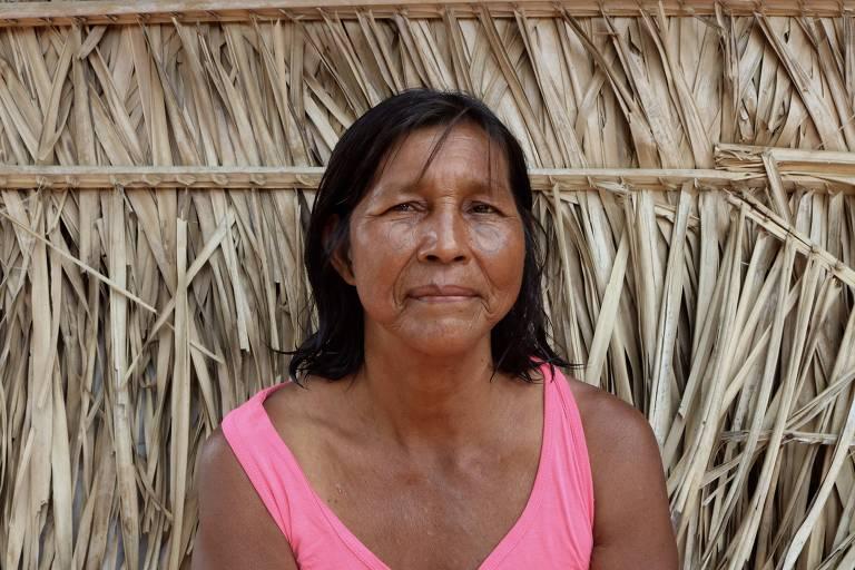 retrato de mulher indígena de regata rosa diante oca