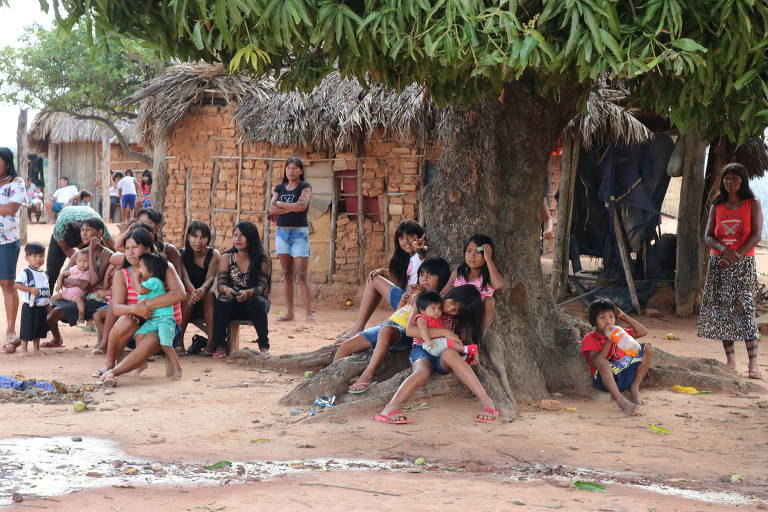 grupo de mulheres e adolescentes indígenas sentado em raízes de árvore e diante de casa de tijolos em chão de terra batida