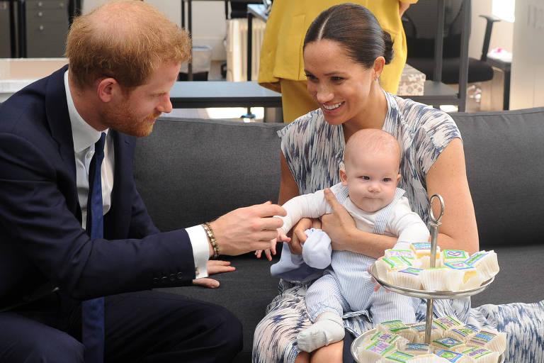 Homem ruivo quase careca de terno toca mão de bebê segurado por uma mulher