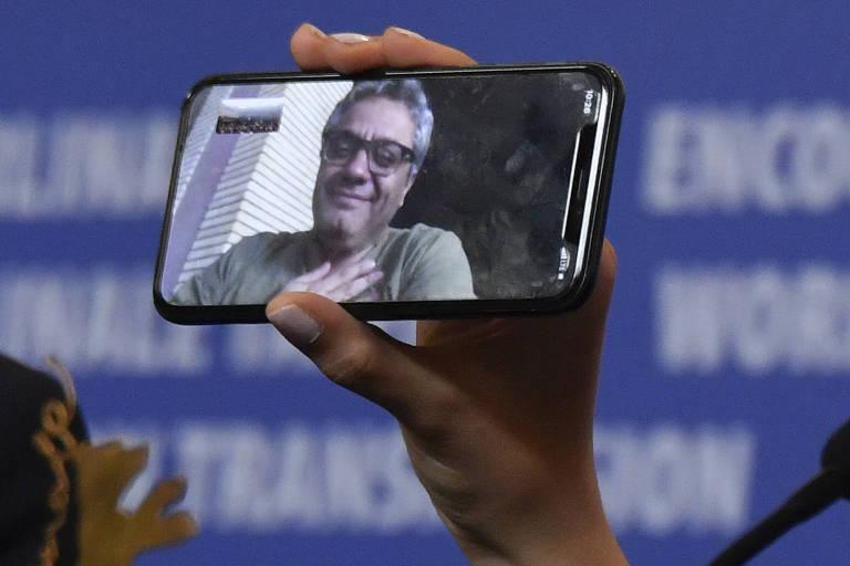 Atriz iraniana Baran Rasoulof mostra, no celular, o pai Mohammad Rasoulof, que não pôde comparecer à premiação do Festival de Berlim 2020