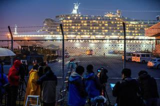A bus arrives near the cruise ship Diamond Princess, where dozens of passengers were tested positive for coronavirus, at Daikoku Pier Cruise Terminal in Yokohama
