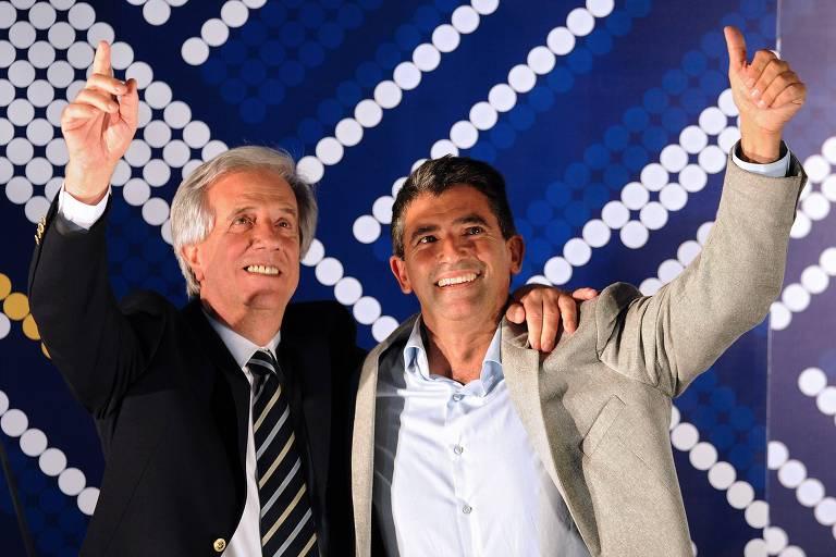 O candidato pelo Partido Frente Ampla, Tabaré Vázquez (esq.), ao lado do seu vice, Raúl Sendic, acenam para eleitores durante a eleição presidencial de 2014 no Uruguai