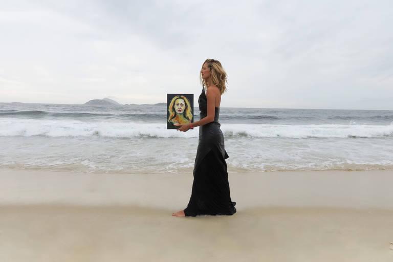 mulher em pé na praia segurando quadro