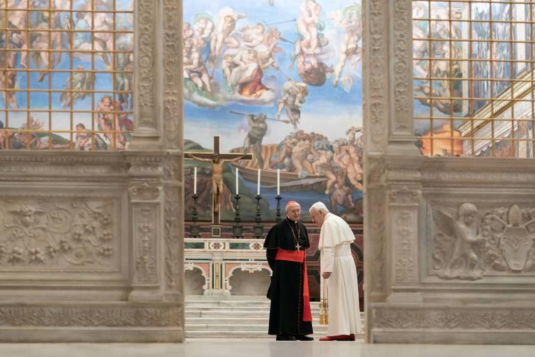 Os atores Jonathan Pryce e Anthony Hopkins, vestidos como os personagens Jorge Bergoglio (atual papa) e Bento XVI, em cenário que reproduz a Capela Cistina, que fica no Vaticano, em Roma