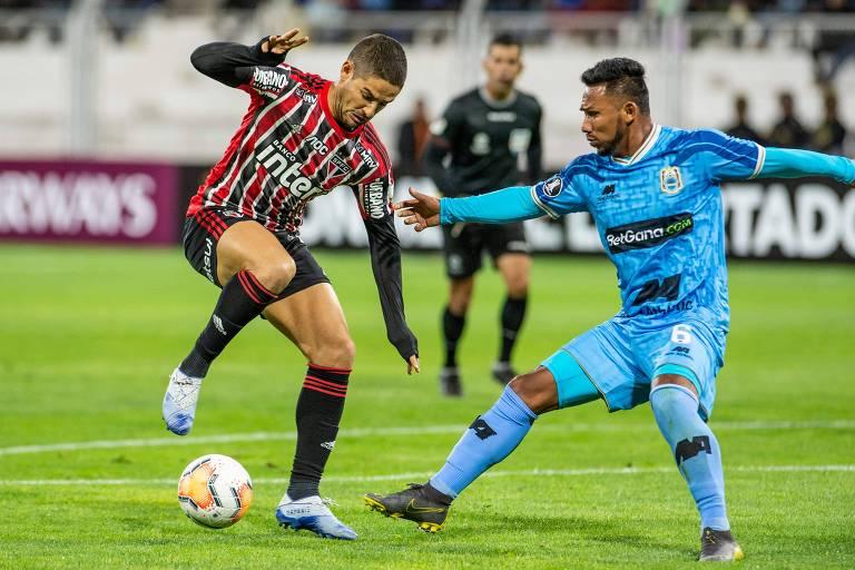 O atacante Alexandre Pato (à esq.) tenta escapar da marcação do meia Angel Ojeda (à dir.)