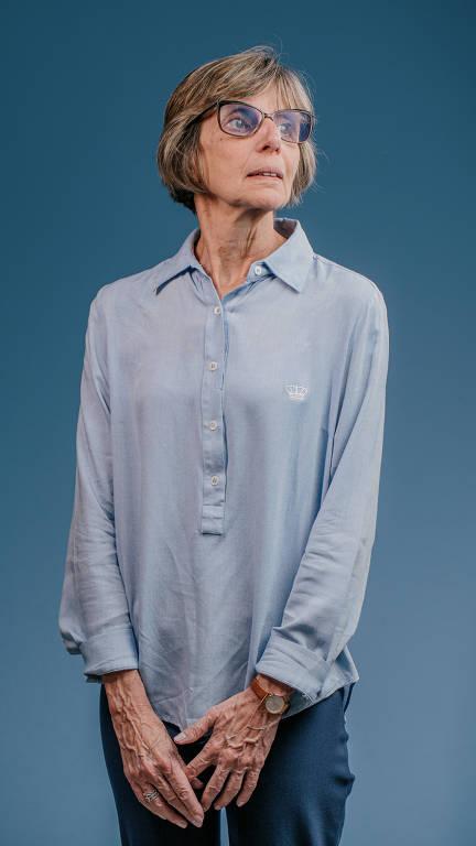Senhora elegante com cabelos cortados pelo ombro, corte channel, usa óculos de grau, veste camisa azul e jeans azul com as mãos unidas na frente do corpo olha para cima para o lado direito