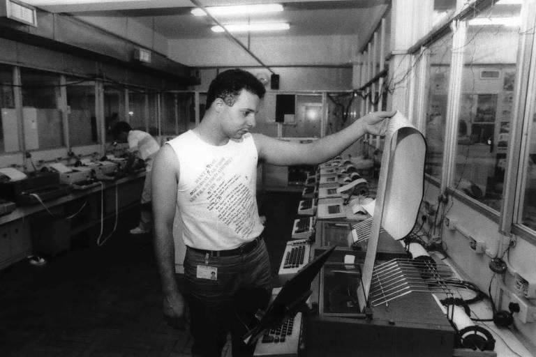 O operador de telex Luigi F. Mathiuzo manuseia telex com a Sucursal de Porto Alegre, no jornal Folha de S.Paulo, nos anos 80. O homem segura um folha comprida que saí de uma máquina telex. A foto é preto e branco