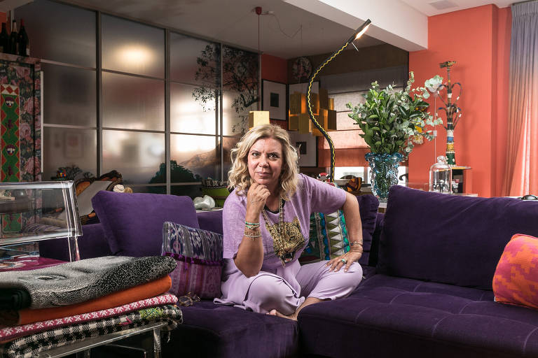 Mulher loira sentada em sofá, com roupas roxas