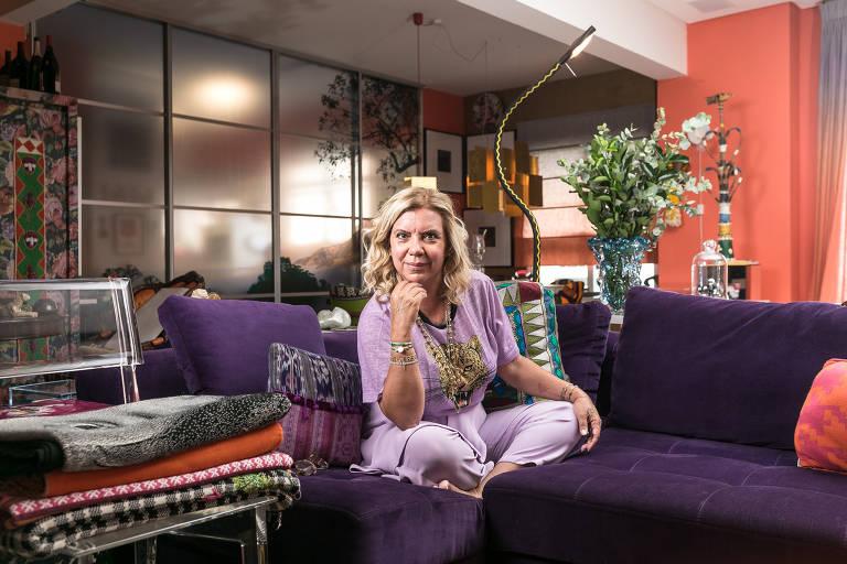 Mulher sentada em sofá roxo, com os cabelos presos e as pernas cruzadas
