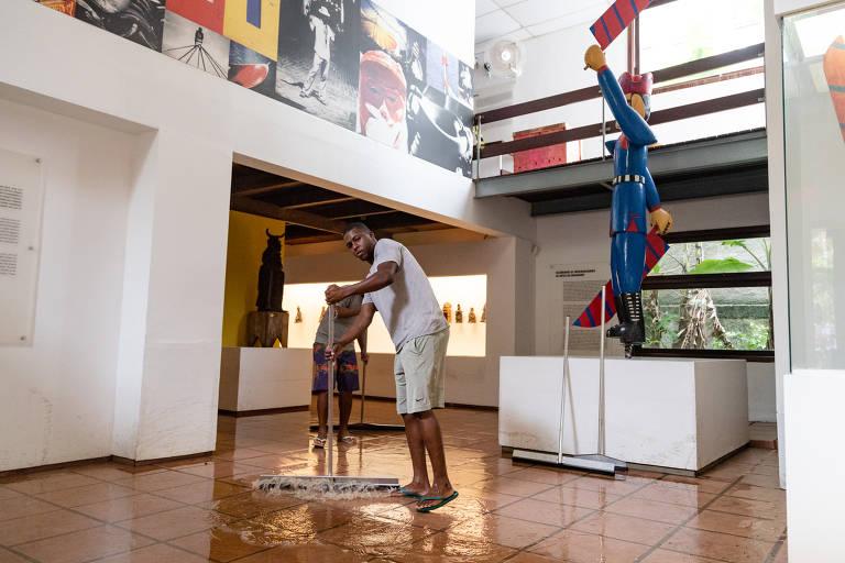 Funcionários trabalham na limpeza do museu após a inundação do dia 1º de março; na foto, vemos um homem torcendo um pano, em primeiro plano, entre obras de arte e vitrines