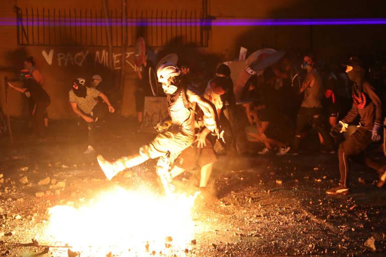Manifestantes em meio a incêndio durante manifestação em Santiago