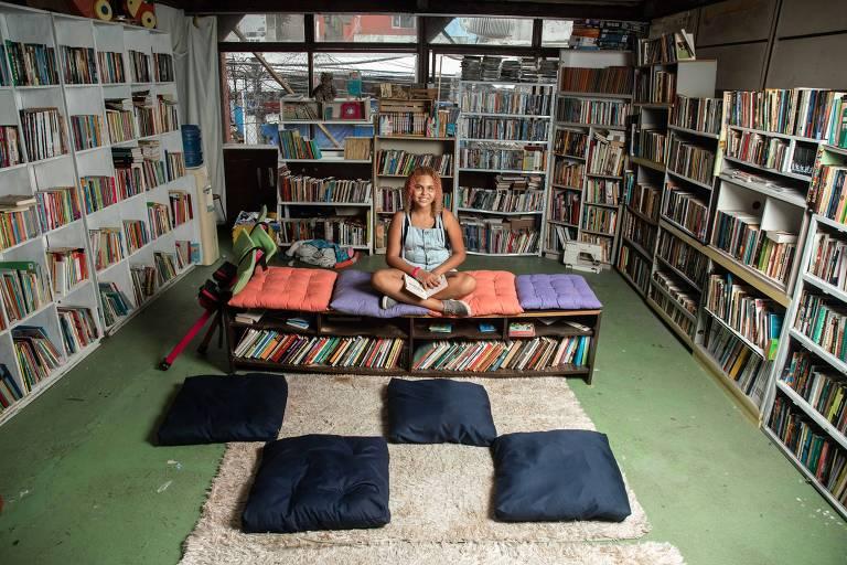 Lua Oliveira, 12, na biblioteca pública com 18 mil livros que criou na associação de moradores do Morro dos Tabajaras, comunidade em Copacabana, na zona sul do Rio