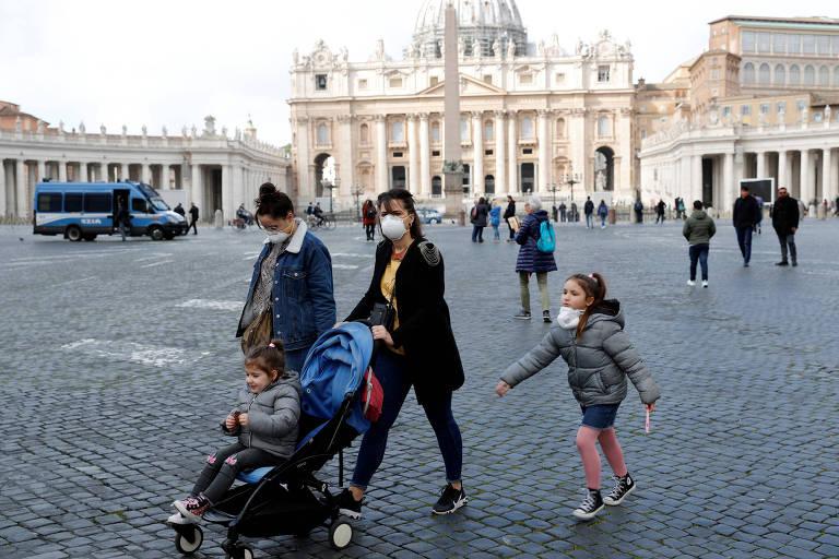 Pessoas usam máscaras na praça São Pedro depois que o Vaticano anunciou seu primeiro caso do novo coronavírus